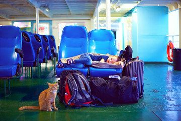 boy sleeps on seats during exhausting journey on ferry boat