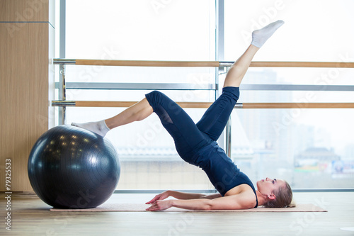 Young girl working out at the gym with a ball