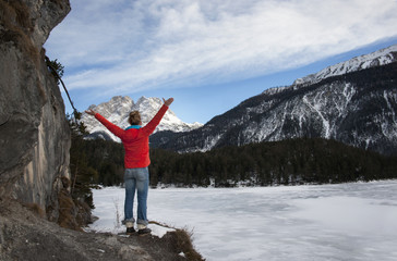 Woman standing by a frozen lake with Zugspitz