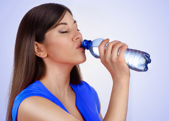 Young woman drinking water from bottle on blue background