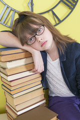 Tired ten years' girl leaning on a stack of books..