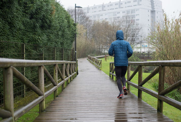 Man running in the park in a rainy day