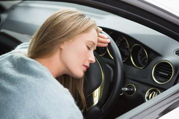 Tired woman asleep on steering wheel