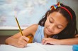 Little girl writing book in classroom - 79333393