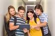 Students using digital tablet at college corridor