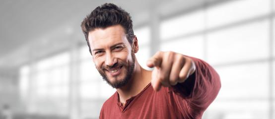 Smiling man pointing at camera
