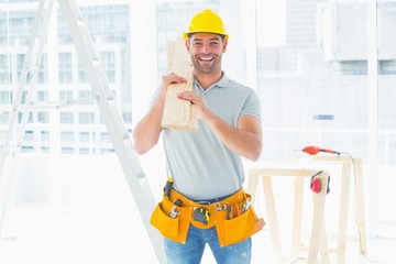 Smiling handyman carrying planks in building