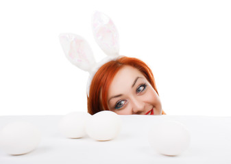 Easter bunny female looking over table for easter eggs