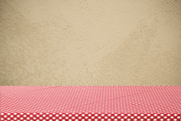Empty table covered with red checked tablecloth over cement wall