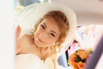beautiful bride smiling in a car