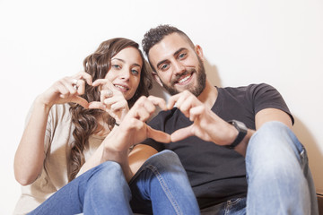 pretty young couple makes heart sign with his hands