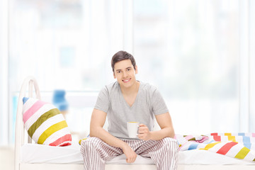 Guy drinking his morning coffee seated on a bed