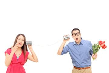 Man and a woman talking through a tin can phone