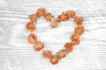 dry rose flowers heart isolated on white wooden panel