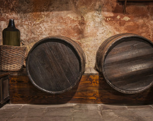Wine cask barrels and bottle stacked in the old cellar of the wi