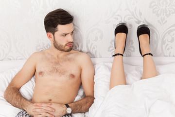 Mann wundert sich über die Liegeposition seiner Frau