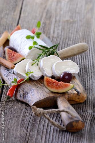 Staande foto Zuivelproducten Cremige Ziegenkäserolle mit Feigen und Oliven