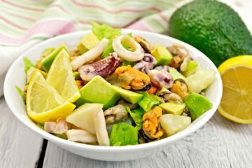Salad seafood and lemon on white board