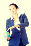 Happy business woman holding small globe.