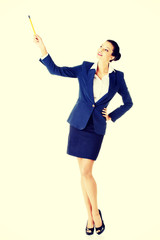 Attractive businesswoman pointing with pencil.