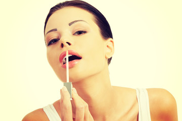 Beautiful young woman applying lipstick.