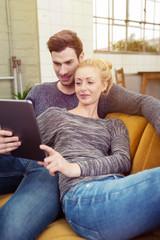 modernes paar liegt auf dem sofa und schaut auf tablet-pc