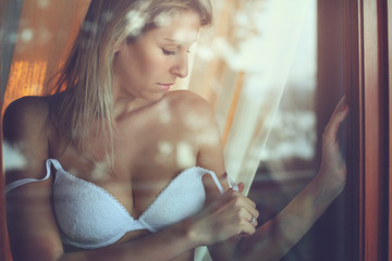Beautiful woman in lingerie at the window