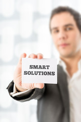 Businessman Holding a Card with Smart Solutions