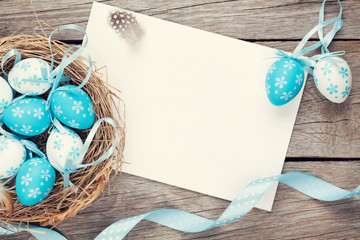 Easter greeting card with blue and white eggs in nest over wood