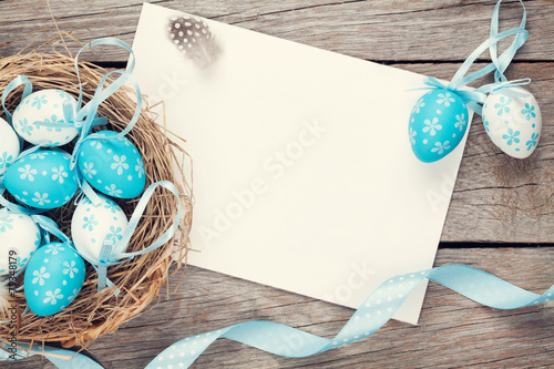 Fotobehang Egg Easter greeting card with blue and white eggs in nest over wood