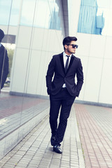 handsome stylish man in elegant black suit and sunglasses