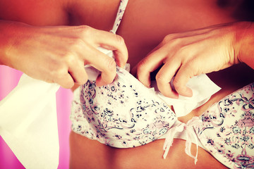 Woman stuffing bra with tissue.