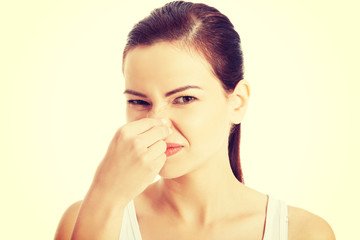 Woman pinches her nose.