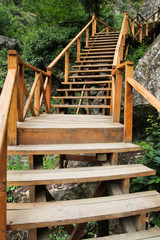 Narrow wooden path suspended over rocks