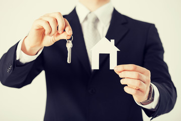 man holding house keys and paper house