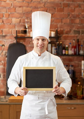 happy male chef with blank menu board in kitchen