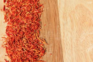 heap of saffron spice on wooden plank background