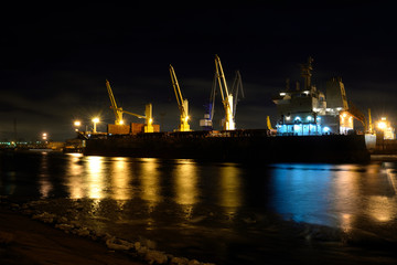 The loading cargo ship with cranes is moored in port at night