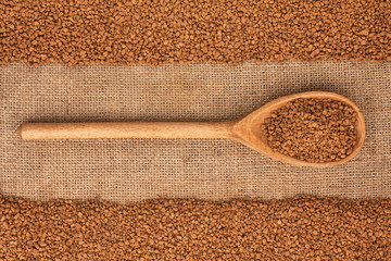 Wooden spoon with granulated coffee lies on  sackcloth