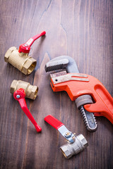 plumbers fixtures and adjustable wrench on vintage wooden board