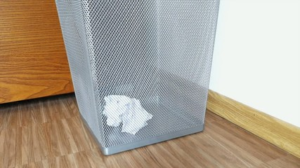 Throwing crumpled paper into the trash