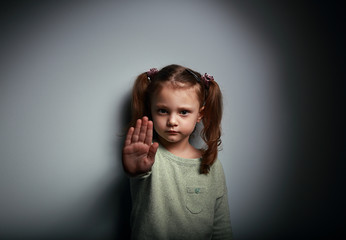 Kid girl showing hand signaling to stop against violence