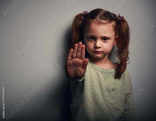 Leinwandbild Motiv Angry kid girl showing hand signaling to stop useful violence