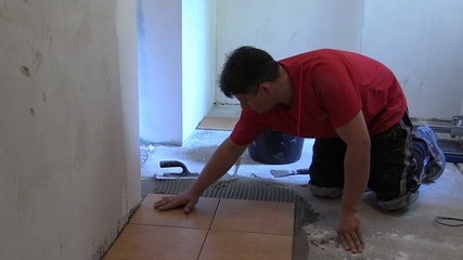 man glue ceramic tile on kitchen floor at home