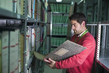 Encargado realista de archivo mira anotaciones en libro
