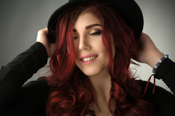 Young woman with professional make up posing with a hat