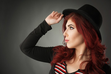 Profile portrait of a cute redhead woman posing with a hat