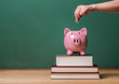 Depositing money in a piggy bank on top of books - 79362556
