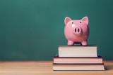 Piggy bank on top of books with chalkboard