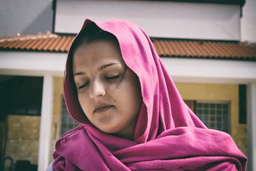 Dark Hair Woman is Praying in Pink Scarf